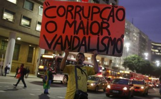 "A man protests Brazilian President Dilma Rousseff's with a sign that reads, ""Corruption, the biggest vandalism."""